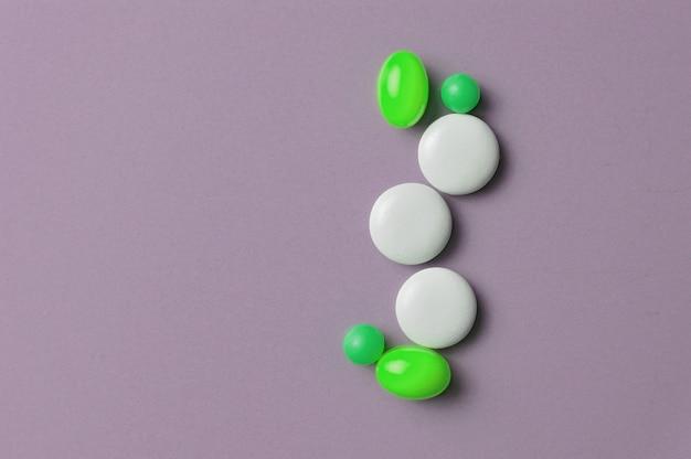 Pillole e vitamine multicolori in capsule su sfondo grigio. vista dall'alto