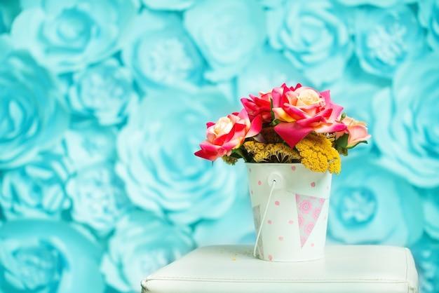 Rose multicolori e fiori secchi in un piccolo secchio leggero con una stampa rosa