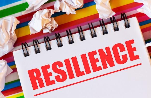 Su uno sfondo a strisce multicolori ci sono pezzi di carta bianca e un taccuino bianco con la scritta in rosso resilienza
