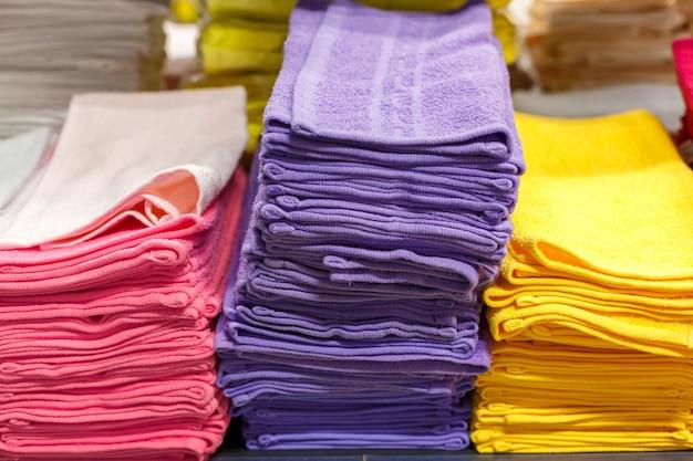 Asciugamani multicolori in pile sullo scaffale del negozio, sezione tessile nel negozio