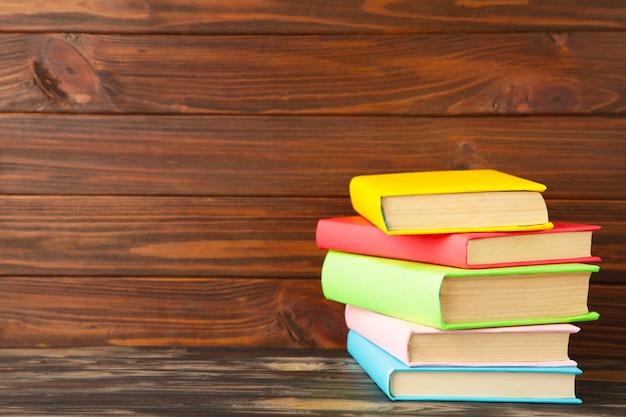 Multi libri di scuola colorati su un fondo di legno marrone con lo spazio della copia. di nuovo a scuola