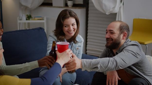 Amici multi-culturali che acclamano le bottiglie di birra durante la festa del fine settimana che ridono mentre si rilassano sul divano a tarda notte. gruppo di persone di razza mista che si divertono a trascorrere del tempo insieme