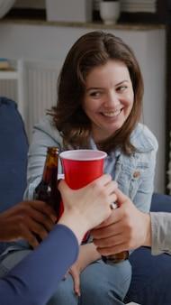 Amici multiculturali che acclamano le bottiglie di birra durante la festa del fine settimana che ridono mentre si rilassano sul divano a tarda notte