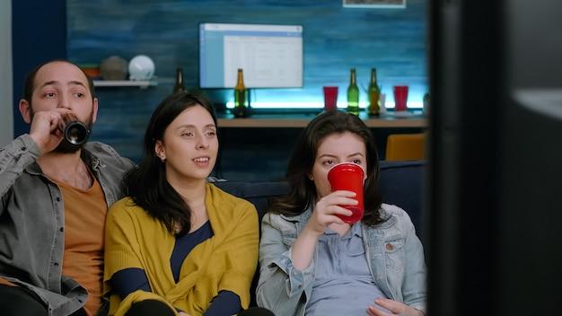 Amici multiculturali che si rilassano sul divano guardando un film divertente in televisione durante la festa notturna in soggiorno. gruppo di persone di razza mista che bevono birra, mangiano spuntini e si godono il tempo insieme