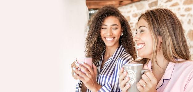 Donne multietniche migliori amiche in pigiama sorridente che tiene una tazza di tè con lo spazio bianco della copia a sinistra - concetto: stai a casa e goditi la vita