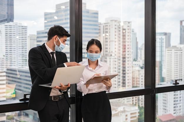 Multi etnico collega di lavoro che indossa la maschera per il viso discutendo e consultando nel nuovo ufficio normale