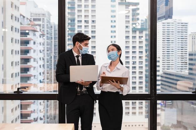 Multi etnico collega di lavoro che indossa la maschera per il viso e sorridente con la discussione nel nuovo ufficio normale