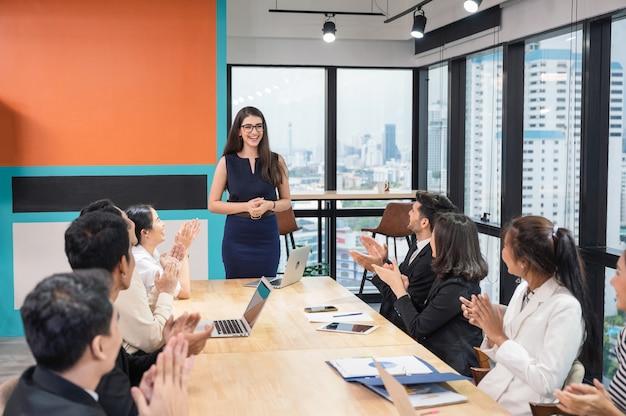 Squadra multietnica di affari che applaude e applaude il successo dell'azienda nell'ufficio moderno