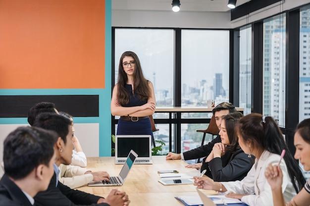 Collega multietnico del team di affari che incontra seriamente e discute sul tavolo da conferenza in ufficio moderno