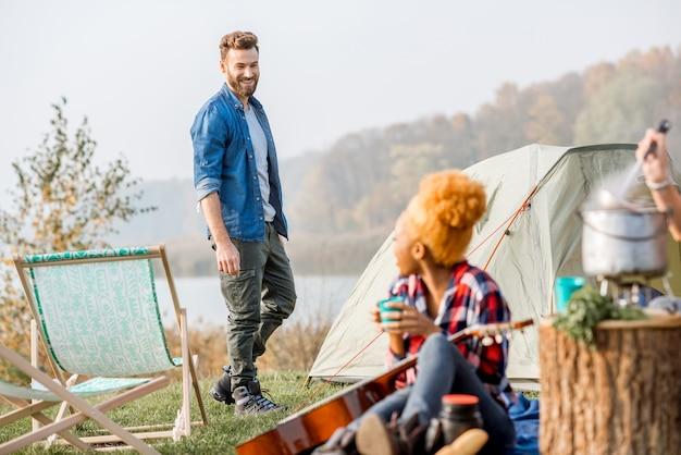 Multi etnico coppia di amici vestiti casualmente parlando durante la ricreazione all'aperto con tenda vicino al lago