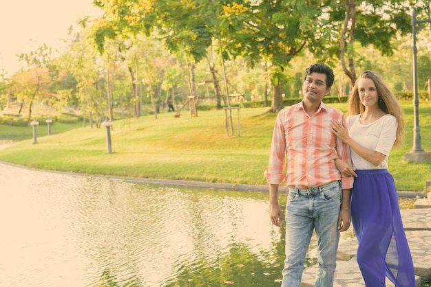 Coppia multietnica pensando stando in piedi sul sentiero di pietra in mezzo al lago in un tranquillo parco verde