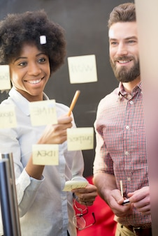 Colleghe multietniche che lavorano insieme con adesivi sulla porta trasparente in ufficio