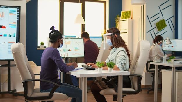 Dipendenti multietnici con visiera e maschera di protezione seduti alla scrivania che analizzano i dati finanziari. donna di colore che prende appunti rispettando la distanza sociale nel nuovo normale ufficio commerciale durante la pandemia globale