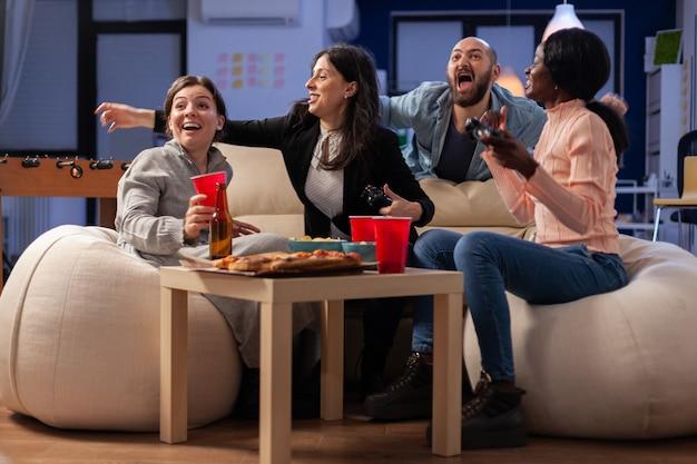 Amici multietnici festeggiano insieme dopo il lavoro in ufficio