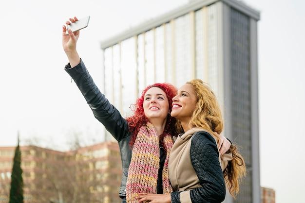 Amici multietnici che si divertono in città prendendo selfie.
