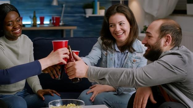 Amici multietnici che trascorrono del tempo insieme, rallegrando bottiglie di birra durante la festa a casa mentre riposano sul divano a tarda notte nel soggiorno. gruppo di persone di razza mista che escono, si divertono conversando