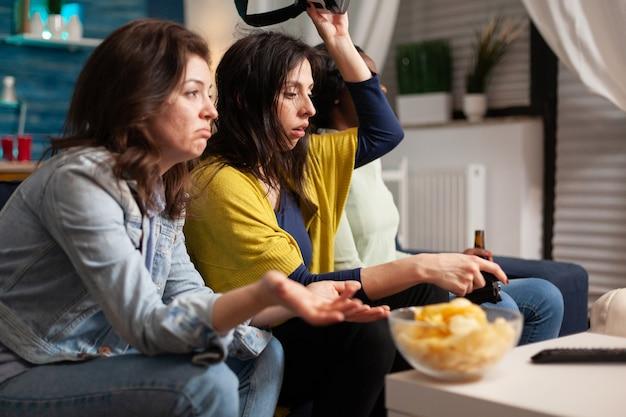 Amici multietnici sconvolti dopo aver perso la competizione di giochi di realtà virtuale seduti sul divano. gruppo di persone di razza mista che escono insieme divertendosi a tarda notte nel soggiorno