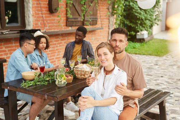 Gruppo multietnico di bei giovani che godono della cena all'aperto alla luce del sole, concentrarsi sulla coppia sorridente in primo piano
