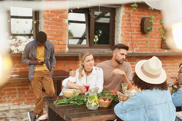 Gruppo multietnico di bei giovani che godono della cena all'aperto alla luce del sole mentre era seduto al tavolo di legno