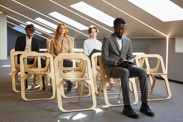 Gruppo multietnico di uomini d'affari seduti su sedie in pubblico di interni contemporanei della sala conferenze, copia dello spazio