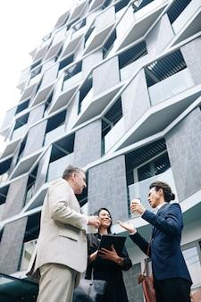 Gruppo multietnico di uomini d'affari in piedi fuori dal moderno edificio per uffici e discutere idee
