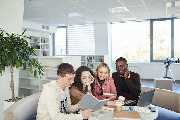 Gruppo multietnico di giovani allegri che studiano insieme seduti a tavola nella biblioteca del college e lavorano su un progetto di gruppo,
