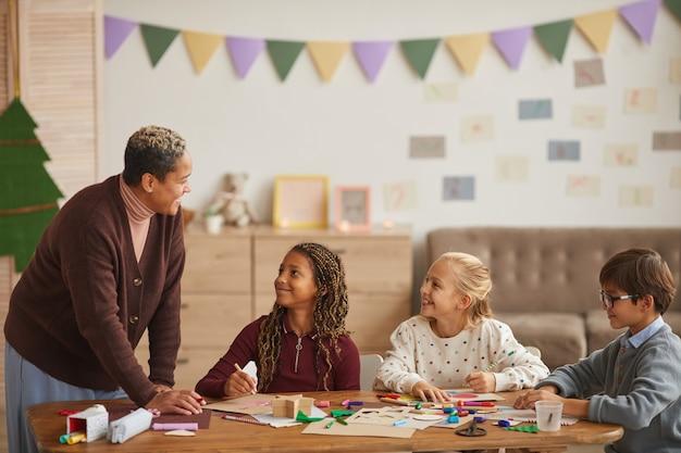 Gruppo multietnico di bambini che disegnano immagini insieme mentre si godono lezioni di arte e artigianato con insegnante femminile sorridente, spazio di copia