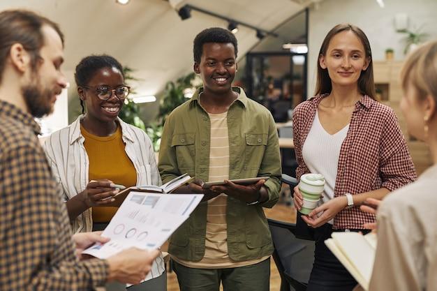 Gruppo multietnico di giovani contemporanei che discutono del progetto di lavoro stando in cerchio in un ufficio moderno e sorridendo allegramente