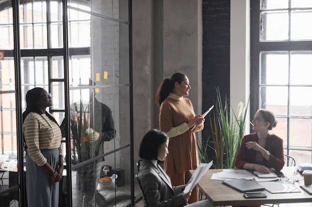 Gruppo multietnico di eleganti donne d'affari che lavorano insieme in interni di uffici grafici, spazio di copia