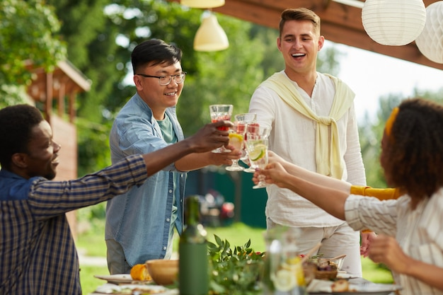 Gruppo multietnico di amici che si godono la cena all'aperto alla festa estiva, concentrarsi su due uomini che tintinnano bicchieri stando in piedi al tavolo