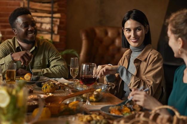 Gruppo multietnico di amici che sorridono felicemente mentre si godono la cena in un'illuminazione accogliente