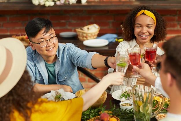 Gruppo multietnico di amici che tostano mentre si gusta una cena all'aperto in estate, concentrarsi sul giovane uomo asiatico che sorride allegramente