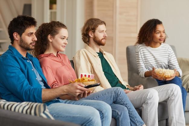Gruppo multietnico di amici che guardano la tv insieme seduti su un comodo divano a casa e si godono spuntini