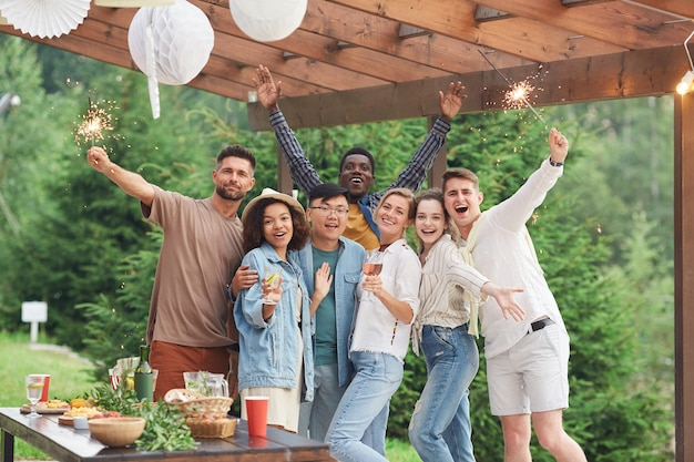 Gruppo multietnico di amici felici che tengono le stelle filanti e godono della festa estiva all'aperto