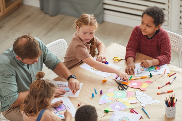 Gruppo multietnico di bambini che disegnano immagini con i pastelli mentre si godono lezioni di arte e artigianato nella scuola materna o nel centro di sviluppo