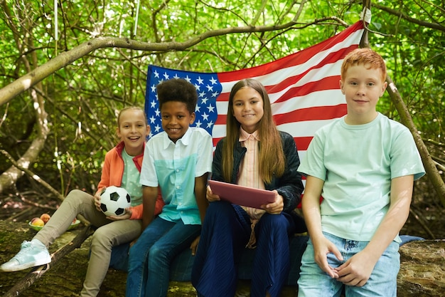 Gruppo multietnico di bambini seduti sotto i rami del grande albero e che giocano nella foresta o nel cortile sul retro