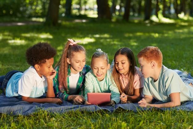 Gruppo multietnico di bambini utilizzando la tavoletta digitale mentre giaceva sull'erba verde nel parco all'aperto illuminato dalla luce solare