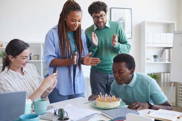 Gruppo multietnico di persone che celebrano il compleanno in ufficio, concentrarsi sul giovane afro-americano che soffia candele sulla torta con i colleghi che applaudono