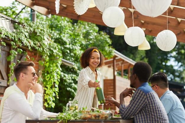 Gruppo multietnico di persone che si godono la cena sulla terrazza all'aperto in estate, concentrarsi sulla sorridente donna afro-americana che consegna una bottiglia di vino sul tavolo