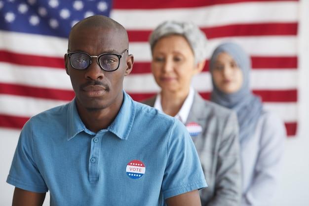 Gruppo multietnico di persone al seggio elettorale il giorno delle elezioni, concentrarsi sull'uomo afro-americano con adesivo ho votato, spazio di copia