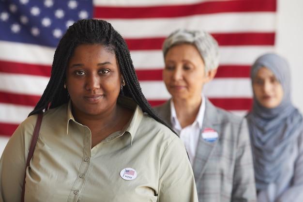 Gruppo multietnico di persone al seggio elettorale il giorno delle elezioni, concentrarsi sulla sorridente donna afro-americana con adesivo ho votato, spazio di copia