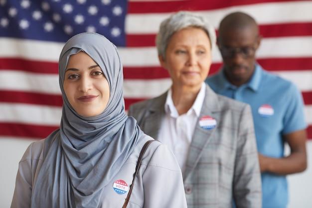 Gruppo multietnico di persone al seggio elettorale il giorno delle elezioni, concentrarsi sulla sorridente donna araba con adesivo ho votato, spazio di copia