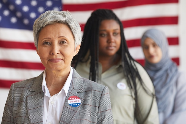Gruppo multietnico di persone al seggio elettorale il giorno delle elezioni, concentrarsi sulla sorridente donna senior con ho votato adesivo, spazio di copia