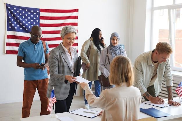 Gruppo multietnico di persone che si registrano al seggio elettorale decorato con bandiere americane il giorno delle elezioni, copia dello spazio