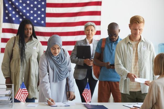 Gruppo multietnico di persone che si registrano al seggio elettorale decorato con bandiere americane il giorno delle elezioni, concentrarsi sulla donna araba che firma modulo di scheda elettorale in primo piano, spazio di copia