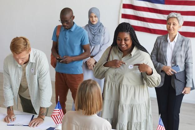 Gruppo multietnico di persone che si registrano al seggio elettorale decorato con bandiere americane il giorno delle elezioni, concentrarsi sulla donna africana sorridente che punta all'adesivo i voto, spazio di copia