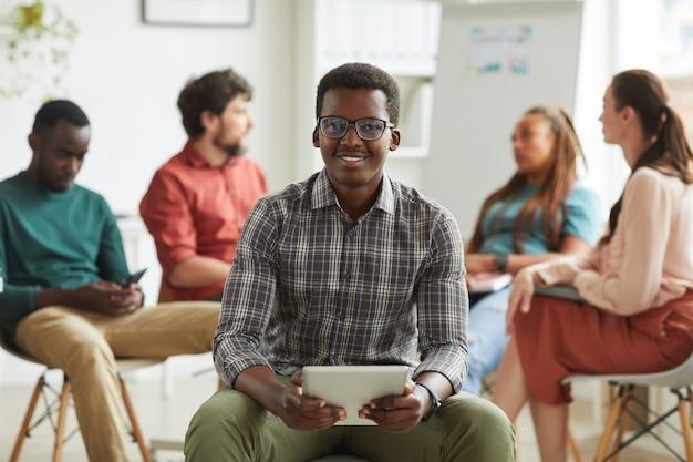 Gruppo multietnico di persone sedute in cerchio mentre discute del progetto di business in ufficio