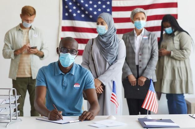 Gruppo multietnico di persone in fila e che indossano maschere al seggio elettorale il giorno delle elezioni, concentrarsi sull'uomo afro-americano che si registra per votare
