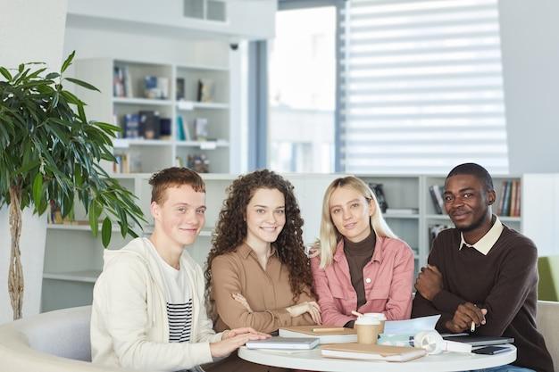 Gruppo multietnico di giovani sorridenti mentre studiano insieme seduti a tavola nella biblioteca del college,