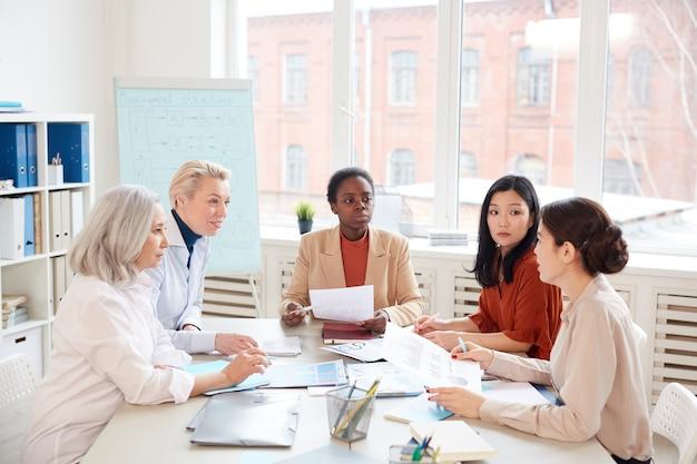 Gruppo multietnico di imprenditrici di successo che discutono del progetto mentre è seduto al tavolo contro la finestra durante la riunione nella sala conferenze